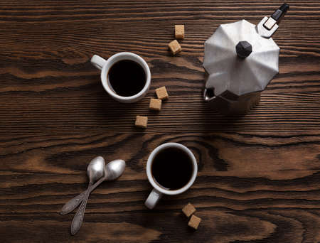 two on top: Two cups of espresso with pieces of cane sugar and Italian  coffee maker on wooden table.