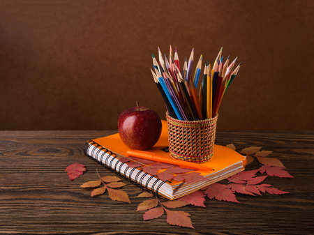 teaching crayons: Colorful pencils, apple  and  dry autumn leaves  on wooden table.