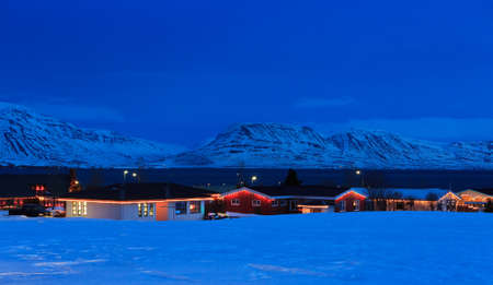 Typical Icelandic houses with Christmas decorations at the twilight near Akureyri, North Iceland.