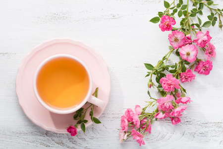 Cup of tea and branch of roses on rustic table.