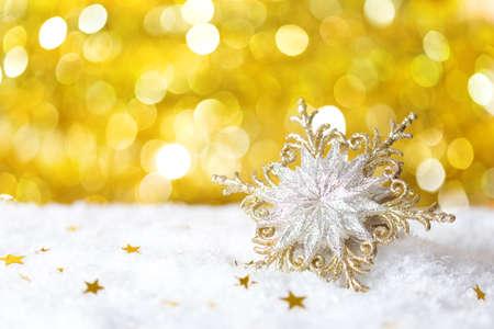 Christmas  snowflake  on yellow  background with sparkles . Stock Photo