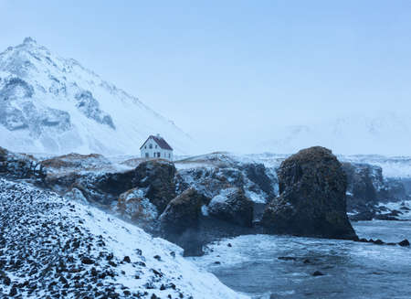 capped: Cliffs near Arnarstapi village at dusk in winter,   Iceland. Arnarstapi  a small fishing village Stock Photo
