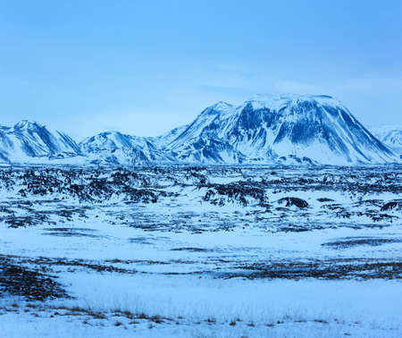 Winter  landscape with lava fields and  the snow capped mountains at dusk, Iceland.  near the Ring Road  (Route 1) of Iceland, between Egilsstadir and  Akureyri