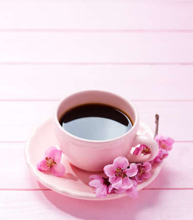 Cup of coffee and spring  flowers  ( peach) on pink wooden table.