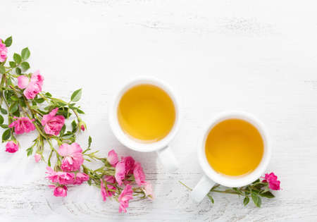 Two cups  of tea and branch of small pink roses on rustic table. Stockfoto