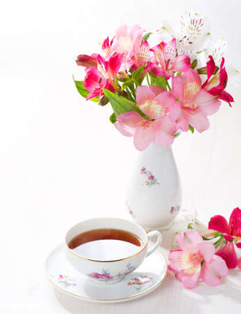 Retro still life with  cup of tea and flowers (Alstroemeria) Stock Photo