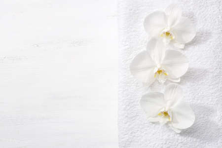 terry: Three orchids and white terry towel  lying on shabby wooden board.  Viewed from above. Spa concept.