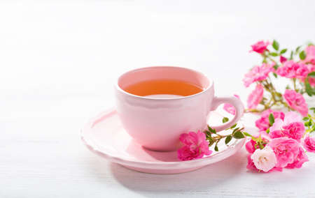 Cup of tea and branch of small pink  roses on rustic table. Stock Photo