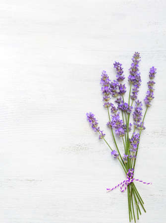 Few sprigs of lavender on  wooden background.