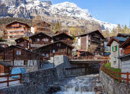 Typical Swiss houses along the Dala river on a spring day in Leukerbad, Valais canton, Switzerland.