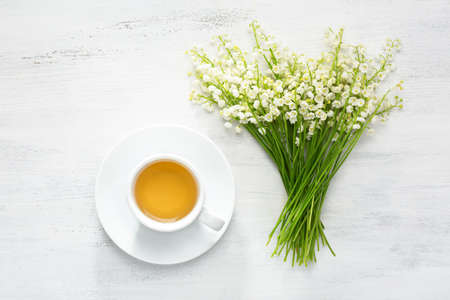 Cup of tea and bouquet of Lilies of the Valley on rustic table.