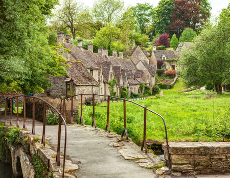 Old footbridge and  traditional Cotswold cottages,   Bibury,  England, UK. Imagens - 79896316