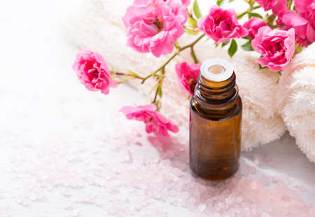Essential oil, Mineral bath salts,  branch  of  small pink  rose  on the wooden table.