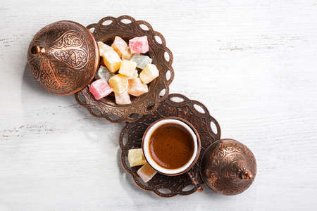 Traditional turkish coffee and turkish delight on white shabby wooden background.  Top view.