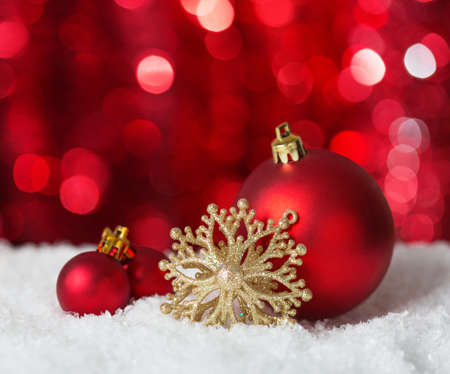 Christmas Baubles on red background with sparkles . Stock Photo