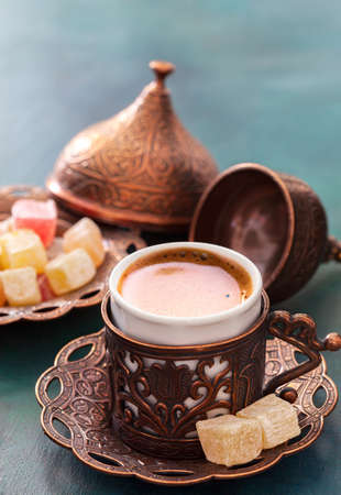 Traditional turkish coffee  and turkish delight on dark green wooden background. Stock Photo