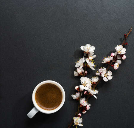 Cup of coffee and spring  flowers  on pink wooden table.