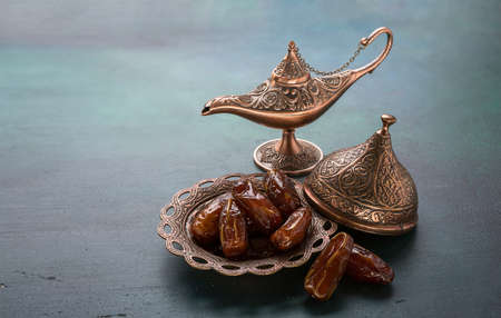 Bronze plate with dates  and aladdin lamp on dark green wooden background. Ramadan background. Ramadan kareem.  Stock Photo