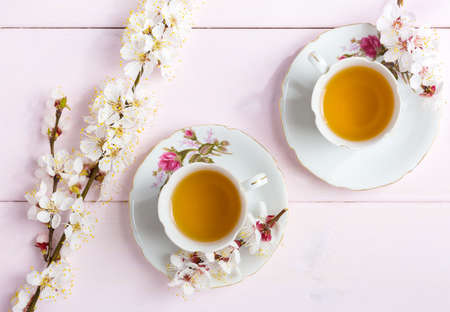 Two cups of tea and spring flowers (blooms of an Apricot) on a light pink wooden table.