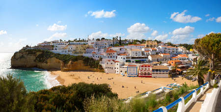 View of the sandy beach surrounded by typical white houses on a sunny spring day, Carvoeiro, Lagoa, Algarve, Portugal.