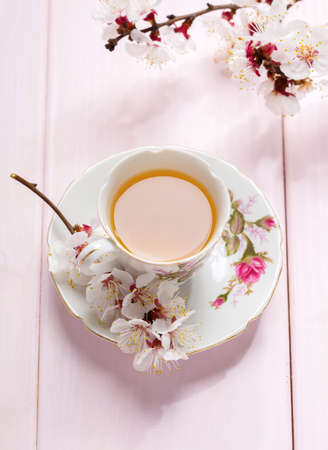 Cup of tea and spring flowers (blooms of an Apricot) on a light pink wooden table.