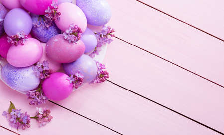 Easter eggs and flowers of Lilac on a pink wooden table.  Top view.