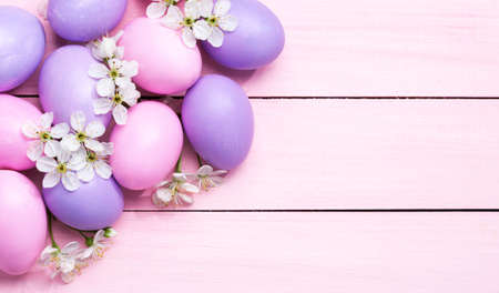 Easter eggs and  white flowers (Cherry blossom ) on pink wooden table.