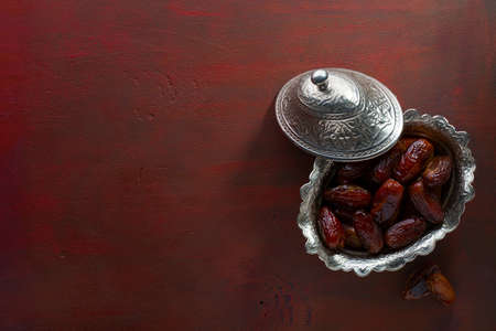 Bowl of dates on a painted  red brown wooden table. Top view