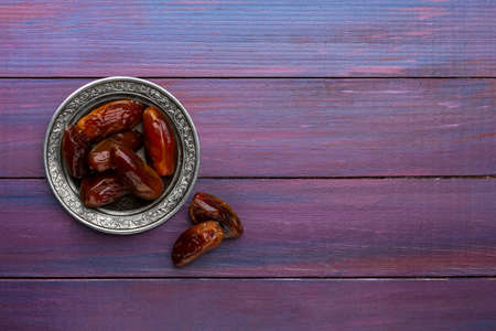 Plate of dates on dark violet wooden background. Flat lay.