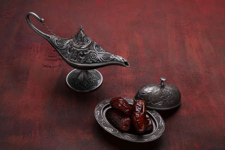 Silver plate with dates  and aladdin lamp on dark red wooden background. Ramadan background. Ramadan kareem.