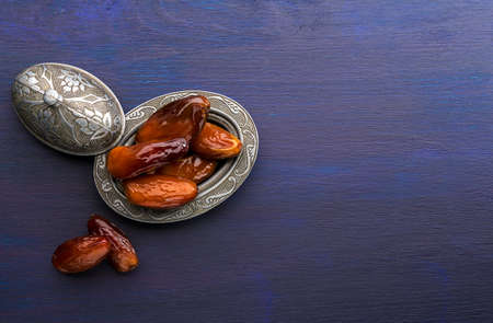 Silver plate with dates  on dark blue wooden background.
