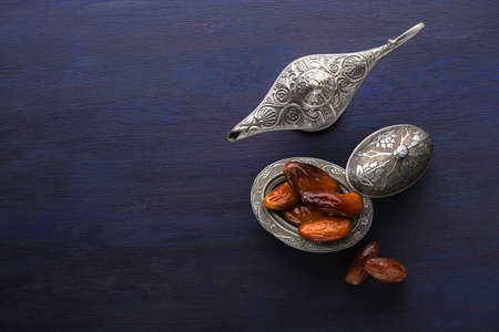 Silver plate with dates  and aladdin lamp on dark blue wooden background. Ramadan background. Ramadan kareem. Imagens