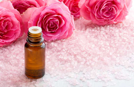 Bottle with essential oil, spa salt crystals and pink roses.