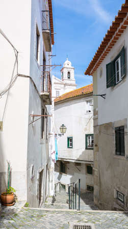 Typical narrow winding street in the Alfama district, Lisbon, Portugal. Imagens