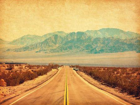 Route 66 attraversando il deserto del Mojave, California, Stati Uniti. Foto in stile retrò. Aggiunta texture della carta. Immagine tonica