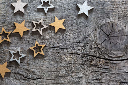 Wooden stars painted in gold and silver color on old wood board  with copy space for text. Wooden  background with Christmas decorations in a rustic style.