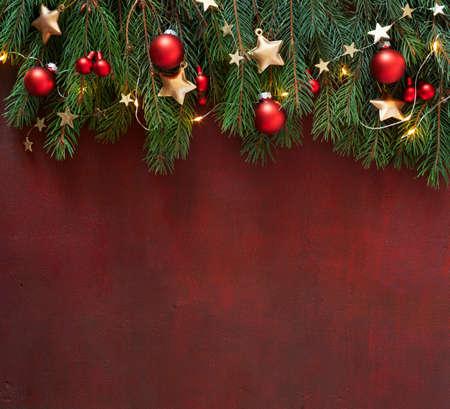 Fichtenzweig mit Weihnachtsschmuck auf dunkelrot lackiertem Holzbrett. Weihnachtshintergrund mit leerem Platz für Text oder Bild. Flach liegen.