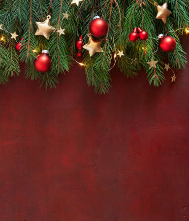 Christmas border with fir branches, red baubles and gold stars on the wooden board painted in dark-red with copy space for text. Flat lay. Christmas and New Year holidays background.