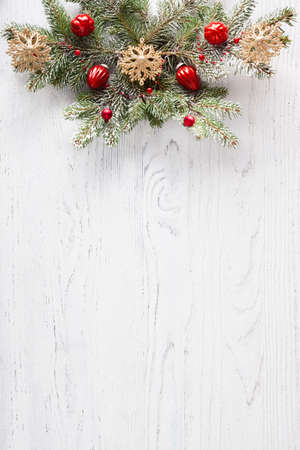 Fir branch with Christmas decoration on white shabby wooden board with copy space for text. Flat lay. Christmas background.