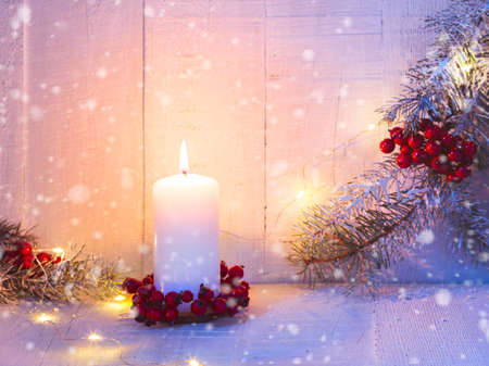 Fir branches, candle and Christmas decorations on the old wooden table. Focus on candle flame
