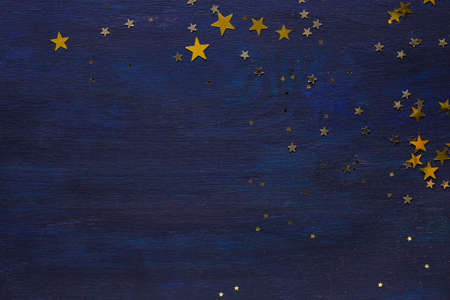 Dark-blue wooden background with golden stars.  Flat lay. Stock fotó