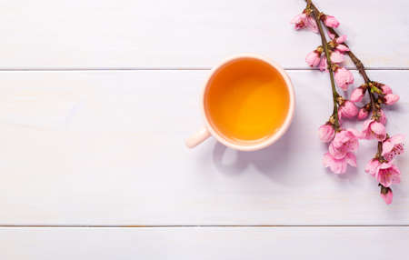 Cup of  tea and  branches of blossoming Peach on  light lilac wooden table with copy space for text.  Flat lay. 免版税图像