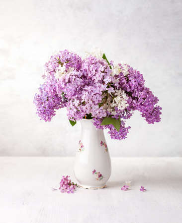 Bouquet of Lilac in old porcelain vase on a white wooden table.  Selective focus.