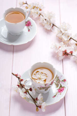 Branches of blossoming Apricot  and Two porcelain cups with tea and on light pink  wooden table. 免版税图像