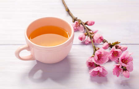 Cup of  tea and  branches of blossoming Peach on  wooden table. 免版税图像