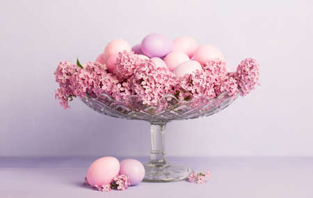 Transparent bowl  with  Easter eggs and flowers of Lilac  on pale light violet  background.  Easter decor