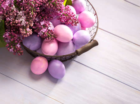 Multicolor Easter eggs and   flowers of Lilac  on  wooden table. Top view.