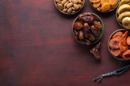 Small plates with dried fruits (date palm fruits, dried apricots, figs) and nuts ( almonds)  for Iftar in Ramadan on the dark red-brown wooden table.  Flat lay.
