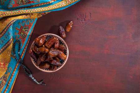 Bronze plate with dates and  tasbih (misbaha) on old red-brown wooden table. Ramadan background.  Flat lay. Selective focus.