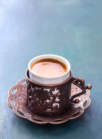 Traditional cup of turkish coffee with foam on dark blue-green wooden background.